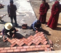 Supervised by monks, workers laid down the bricks at the start of our project at Langyi Monastery